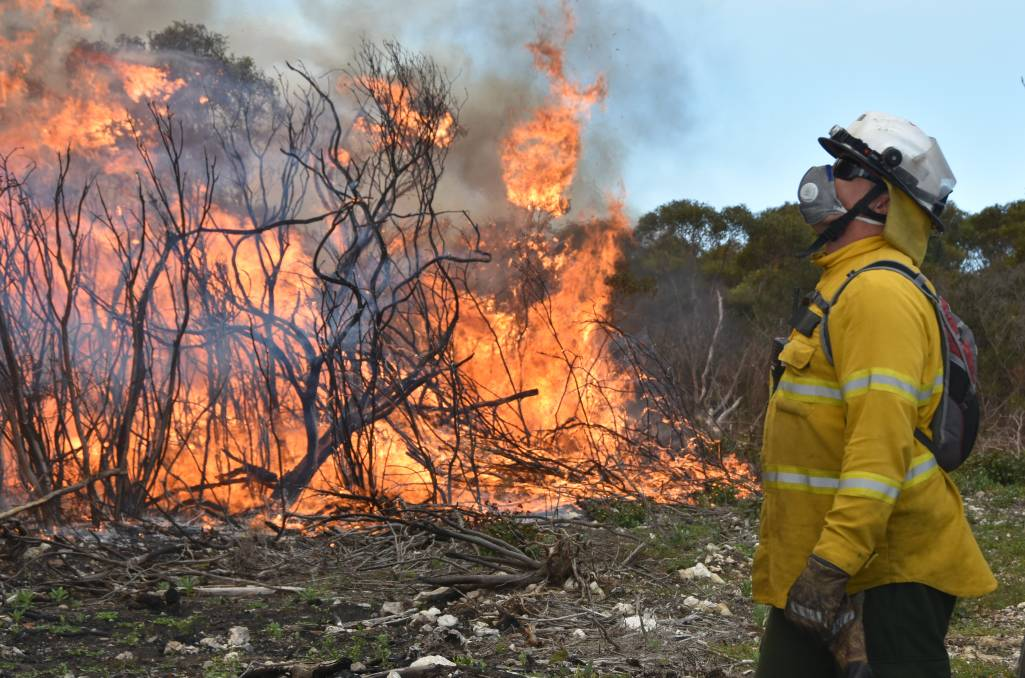 BURN OFF: Firefighter David Booker observes the burn off on SA Water land near Tulka last Wednesday. Photo - Jarrad Delany.